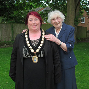 Councillor Marlene Bennett MBE stood with her hands on the shoulders of Mayor Mary Kerry, both smiling.